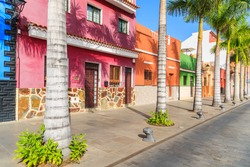 Colourful houses and palm trees on street in Puerto de la Cruz town, Tenerife, Canary Islands, Spain