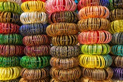 Colourful Indian wrist bracelets stacked in piles on display at a shop in Jaisalmer, India.