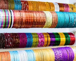 Colourful Indian wrist bracelets stacked in piles on display at a shop in Little India in Singapore. Colorful urban concept