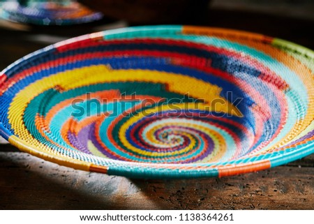 Colourful indigenous woven African bowl with a bright spiral patter in a close up low angle cropped view