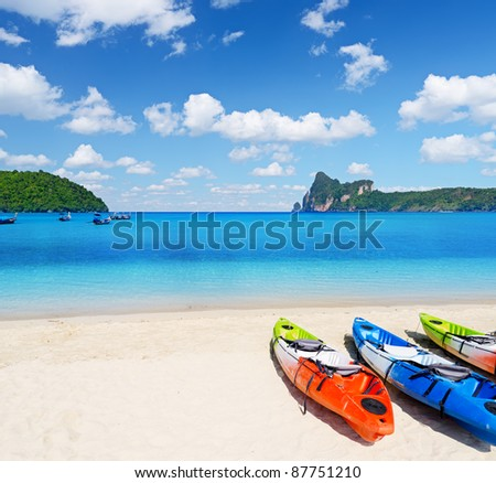Colourful kayaks on tropical beach.