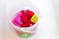 Colourful laundry in a transparent bucket ready for washing