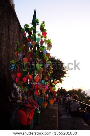 colourful leaves on decorative tree reflect sunlight at the buddhism golden stupa: PHU-SI or PHOUSI monument under twilight sky at evening time in LUANG PRABANG, LAOS #1365201038