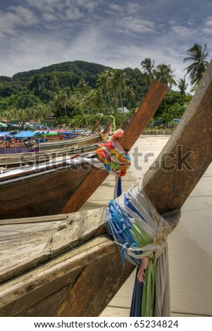 Colourful long tail boats on palm tree covered beach, Thailland