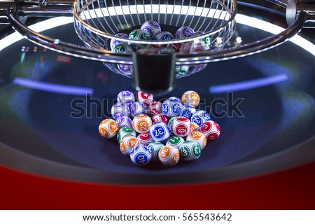 Colourful lottery balls in a rotating bingo machine.