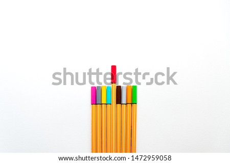 colourful markers as a symbol of difference and creativity between individuals with one red marker marker higher than others