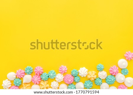 Colourful Meringue in various star shapes on yellow background with space for text. Sweet meringues flat lay. Dessert Background, festive sweets for candy or cake shop concept. Homemade meringue. Foto d'archivio ©