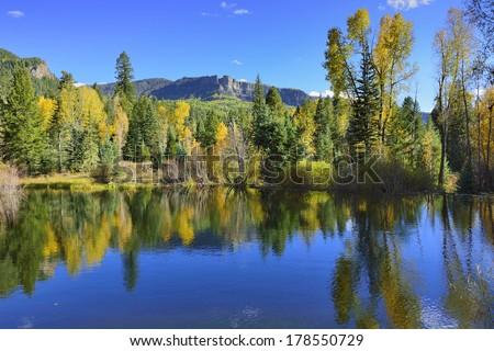 colourful mountains of Colorado reflecting in a lake during foliage season