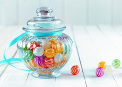 Colourful multicoloured striped candy in a decorative glass jar with a ribbed bulbous shape and a blue ribbon around the neck for a festive gift