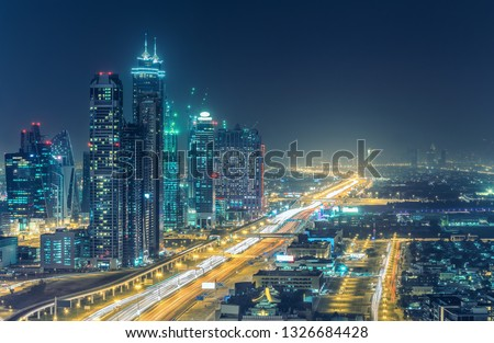 Colourful nightime skyline of Dubai, United Arab Emirates. Aerial view on highways and skyscrapers. #1326684428