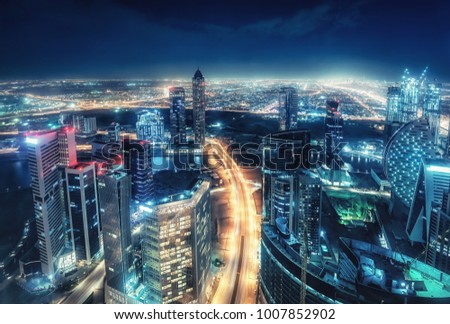 Colourful nighttime skyline of a big modern city. Dubai, United Arab Emirates. Aerial view on highways and skyscrapers. #1007852902