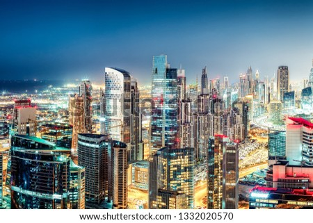 Colourful nighttime skyline of a big modern city. Dubai, United Arab Emirates. Aerial view on highways and skyscrapers. #1332020570