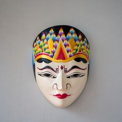 Colourful painted puppet wooden mask hanging on the wall, photographed at close range with large copy and text space - Image.