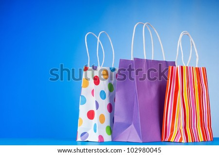 Colourful paper shopping bags against gradient background