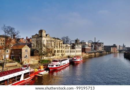 Colourful passenger ferries moored on the bank of the River Ouse in York waiting to take tourists on a sightseeing cruise
