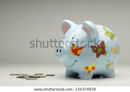 Colourful piggy bank with money isolated on plain background