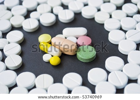 Colourful pills surrounded by white round pills on the black surface