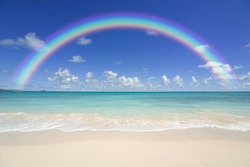 Colourful rainbow over a blue ocean with sandy beach in the foreground