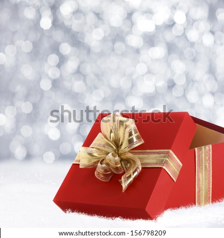 Colourful red Christmas gift decorated with a gold ribbon and bow in winter snow with a bokeh of falling snowflakes and copyspace for your seasonal greeting