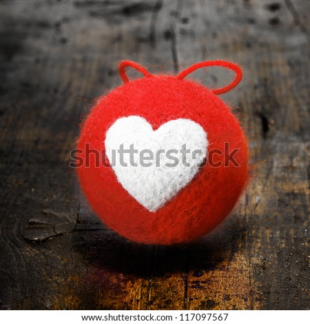 Colourful red textile Christmas bauble with a bold white heart design on an old grunge wooden table in square format for your seasonal or Valentines greeting