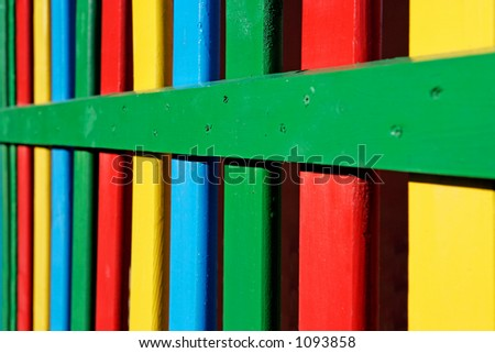 Colourful rows of painted wood on a playground fence with yellow, green blue and red colors - stock photo