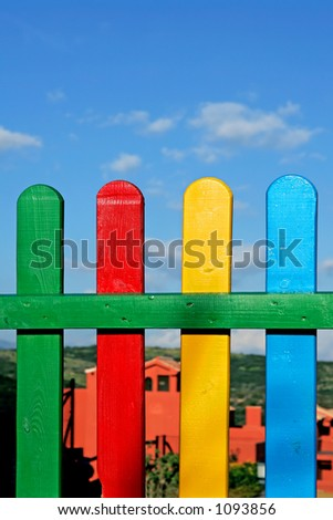 Colourful rows of painted wood on a playground fence with yellow, green blue and red colors and sunny blue sky