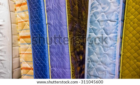 Colourful second-hand mattresses at a thrift store.