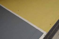 Colourful sections of a parking lot surface in grey and yellow surface with thick white outlines good for background with space for runaround or wraparound text