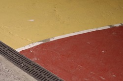 Colourful sections of a parking lot surface in red and yellow with thick white outlines good for background with space for runaround or wraparound text