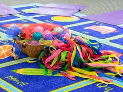 Colourful Sensory Baby Toys in a Basket On a Colourful Childrens Mat, Set up For Baby Massage/Baby Yoga