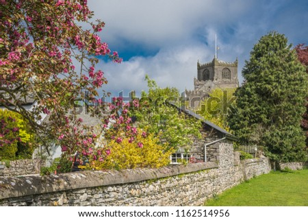 Colourful setting of Cartmel Priory in Cartmel. Dry stone wall, little grass, trees. Stock photo ©