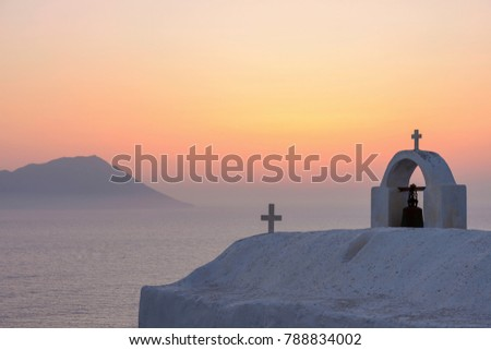 Colourful sky after sunset with an iconic white church in the Greek Islands. #788834002