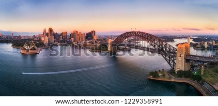 Colourful sky over Sydney city CBD high-rise towers at sunrise around Sydney harbour and the Sydney Harbour bridge in elevated aerial panorama.