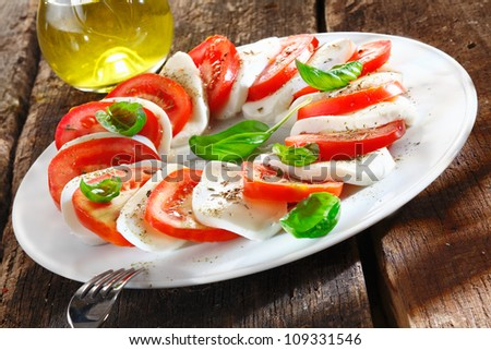 Colourful slices of cheese and tomato arranged alternately on a plate and garnished with herbs served with an oil dressing for drizzling