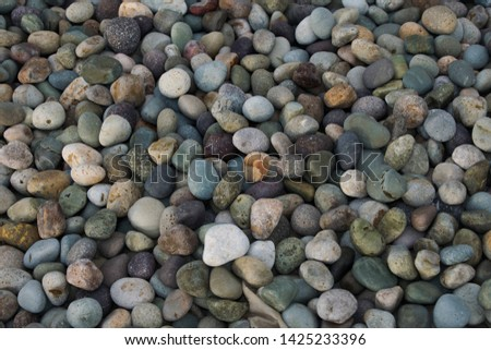 Colourful smooth beach rocks or pebbles. round pebbles piled together