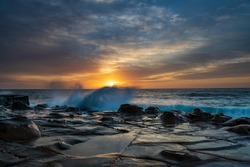 Colourful sunrise seascape with high cloud and tessellated rock platform at North Avoca Beach on the Central Coast, NSW, Australia.