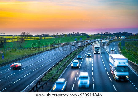 Colourful sunset at M1 motorway near Flitwick junction with blurry cars in United Kingdom.