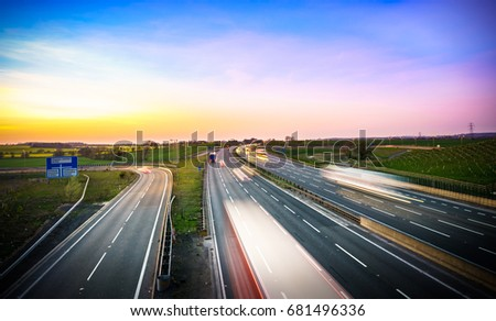 Colourful sunset at M1 motorway near Flitwick junction with blurry cars in United Kingdom