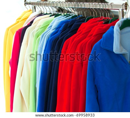 Colourful Textile sport shirts hanging in row at store