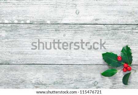 Colourful traditional Christmas holly with with red berries on grunge wood texture of old weathered boards with copyspace
