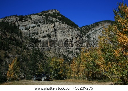 Colourful trees against rocky mountain; parked jeep; autumn/fall; bright blue sky; Alberta, Canada