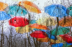 colourful umbrellas and rainy window. fall season. rain drops on wet glass in autumn day.