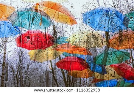 colourful umbrellas over rainy window. texture of autumn umbrellas and wet glass. autumn season. rain outside window on rainy  autumn day. texture of raindrops, wet glass.