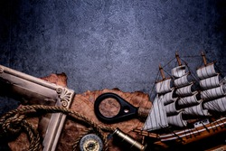 Columbus Day. Pirates and treasure with worldmap and discovery equipment. Copy space on dark background.