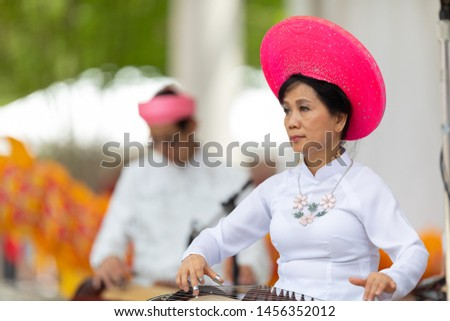 Columbus, Ohio, USA - May 26, 2019: Columbus Asian Festival, Franklin Park, vietnamese woman wearing traditional clothing playing the Dan Tranh at the asian festival #1456352012