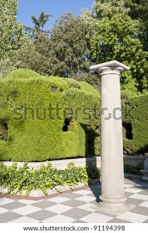 Column and garden. Picture taken in Cecilio Rodriguez Gardens, Retiro Park, Madrid, Spain