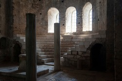 Column hall made of stone in some old castle or church with arches and okras