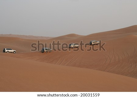 Column of jeeps travelling in sand dunes