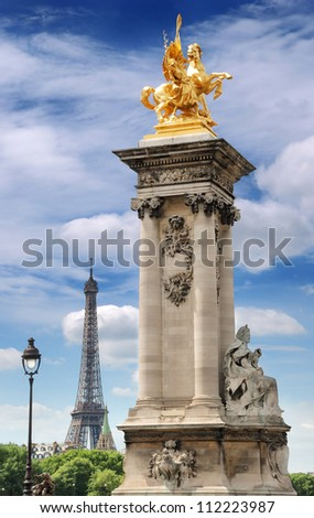 Column with gilded sculpture on the Pont Alexandre III bridge and Eiffel Tower in Paris, France.