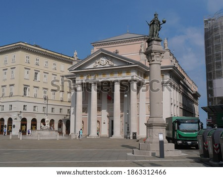 column with the statue of emperor Leopold in Trieste, in front of Neptune fountain and Palazzo della Borsa Stock fotó ©